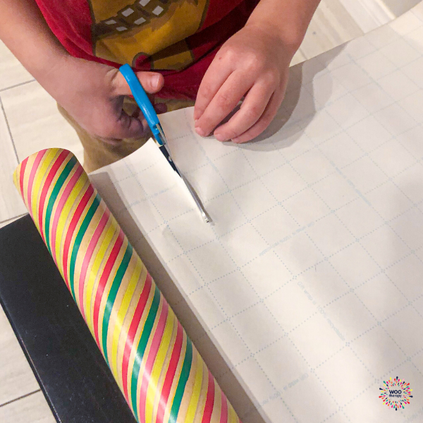 Child using appropriate scissors and guide marks to cut paper in preparation for gift wrapping.