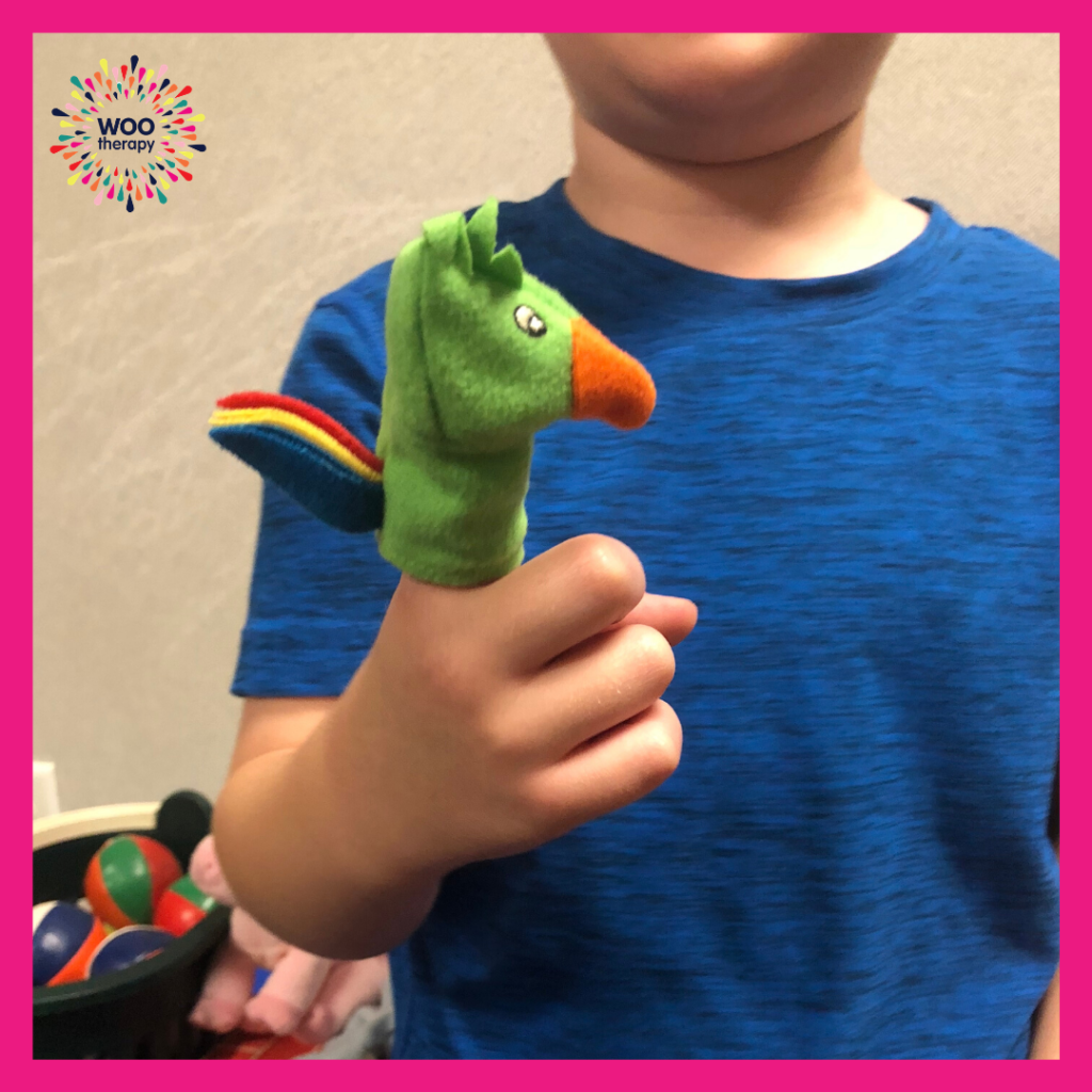 A child using his pointer finger to play with a finger puppet.