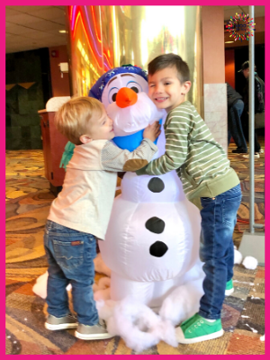 Kids hugging a character while going to see a movie on Christmas Day.
