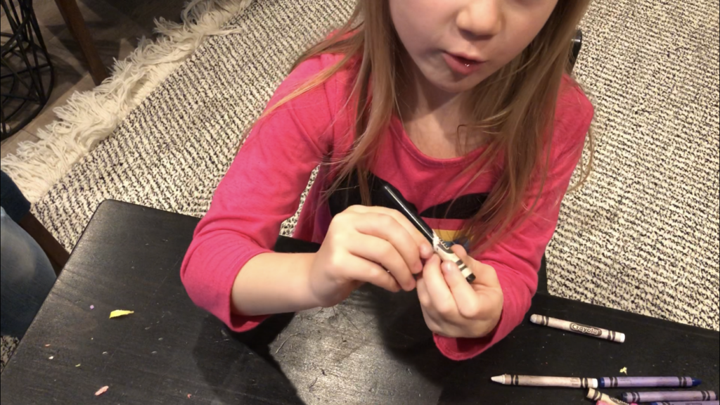 A little girl peeling the paper off of old crayons