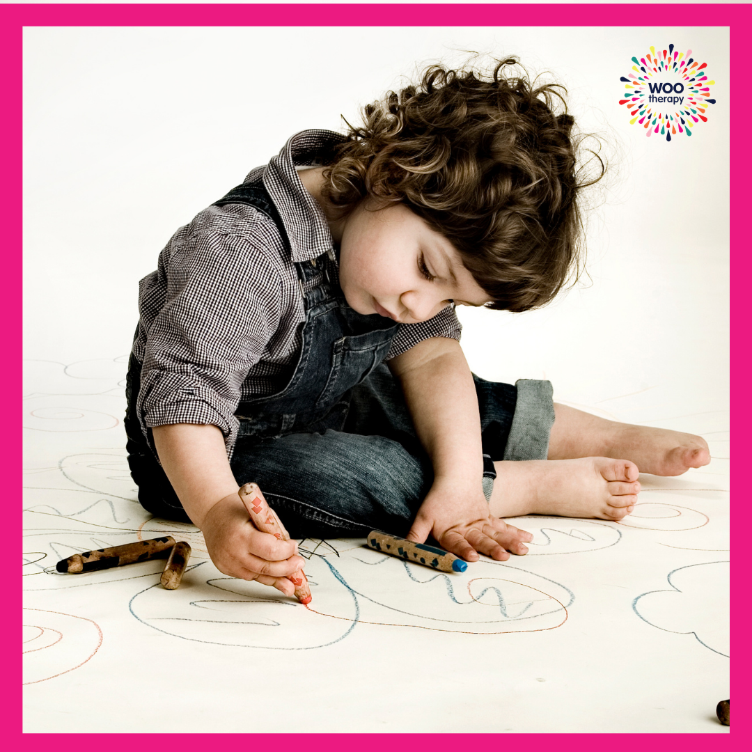 Child using a crayon with all his fingers