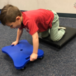 """Child using two scooter board to """"inchworm"""" to the other side of the room"""