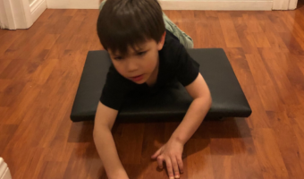 A boy on his tummy using his hands and upper body to propel a scooter board.