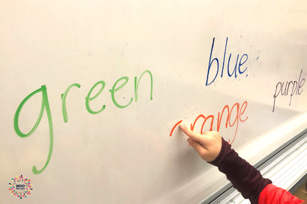 A child using a pointer finger to trace and erase marker off a white board.