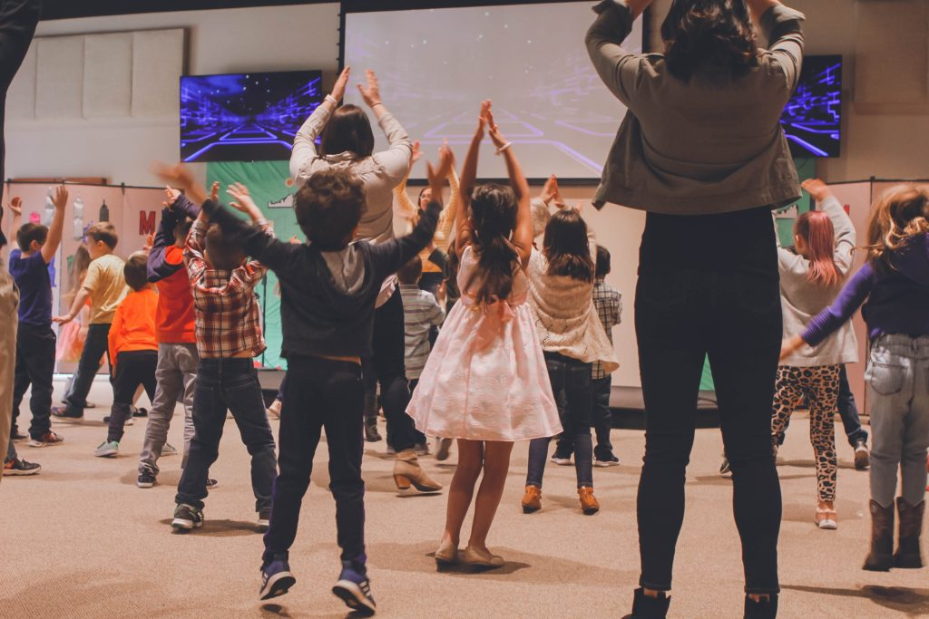A class of 6-7 year old children imitating songs with hand motions as a whole group experience.
