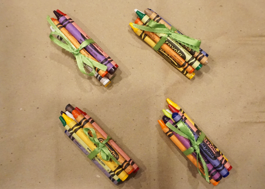 Eight gently used and repurposed crayons tied up with a ribbon as a gift to new students
