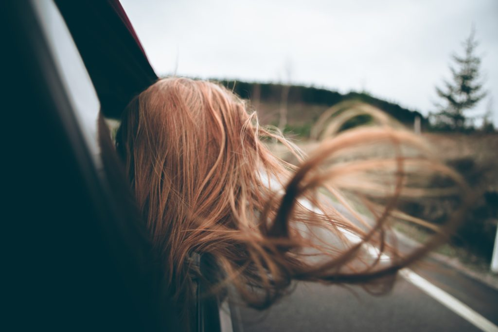 A girl leaning out of the car window on a road trip with her hair whipping around listening to nostalgic music on the radio.