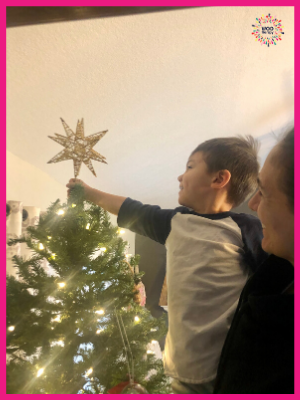 Holiday tradition of a child helping place the star at the top of the Christmas tree.